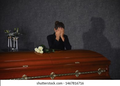 Sad young woman mourning near casket with white roses in funeral home