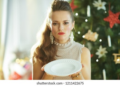 sad young woman near Christmas tree holding empty dinner plate