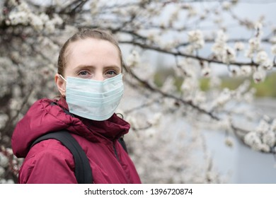 Sad young woman in protective medical face mask. Blooming tree on background. Spring allergy.