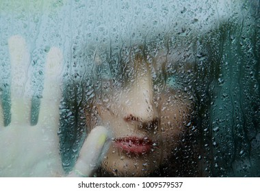 Sad young woman and a rain drops.