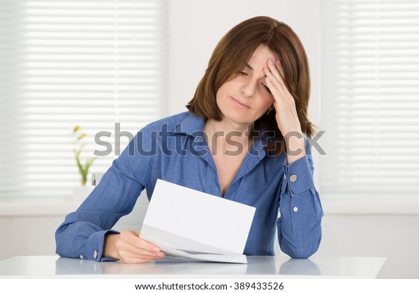 Sad Young Woman Reading Document In Office