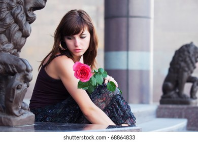 Sad young woman with red rose.