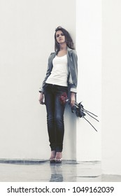 Sad young woman with red roses standing at the wall Stylish fashion model in grey blazer and dark blue jeans