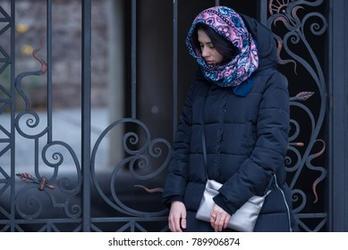 Sad young woman, in a scarf, stands on the background of a vintage wrought-iron gate in the courtyard of an old building. Winter day in the city.