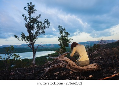 A sad young woman is sitting on a hill burned by a wild fire