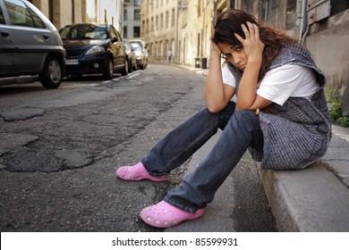 sad young woman sitting on sidewalk in city