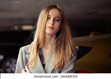 sad young woman at underground parking looking at camera