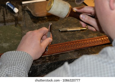 Saddelry - the craft of making saddles and leather equipment for equines. Saddler demonstrates stamping on leather.