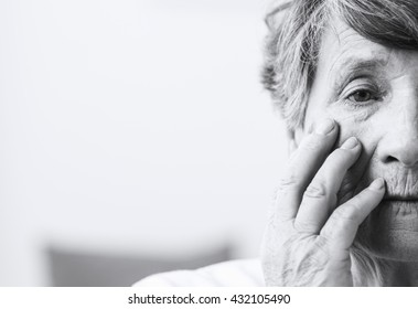 Saddened and afraid  older woman is touching face