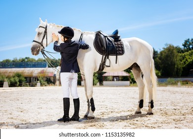 Saddle horse. Appealing dark-haired woman wearing white trousers and dark helmet standing near white saddle horse