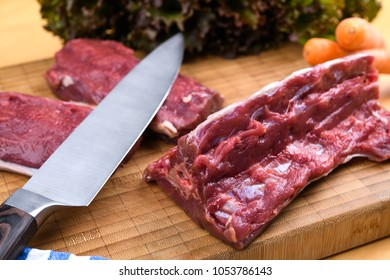 saddle of venison on wooden board with big knife