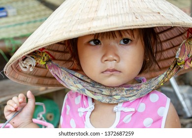 Sadec, Vietnam - March 7, 2019 :  Small girl in traditional straw hat in rural village in Mekong River Delta in Vietnam.