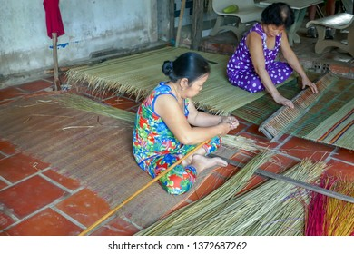 Sadec, Vietnam - March 7, 2019 :  Woman making traditional reed sleeping mats on loom  in rural village in Mekong River Delta in Vietnam.