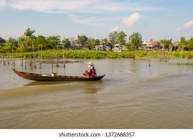 Sadec, Vietnam - March 7, 2019 :  Woman in boat next to fishing nets and village on shores of Mekong River in Vietnam.