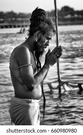 A SADHU IN PRAYER, ALLAHABAD, INDIA - FEBRUARY 17, 2013: A holy yoga sadhu in prayer in Ganges river at Maha Kumbh Mela in Allahabad, India