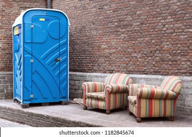 A sadly neglected city corner with blue chemical toilet and two armchairs with a multi-colored striped fabric lining.