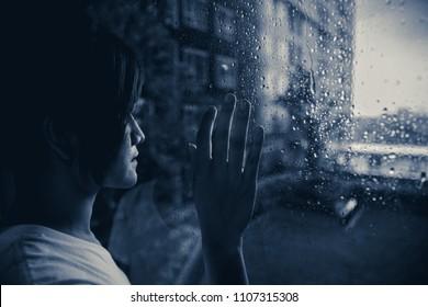 sadly woman looking out at windows raining drops dark mood dim light