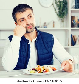 Sadly young man before eating vegetable salad from plato at table indoors