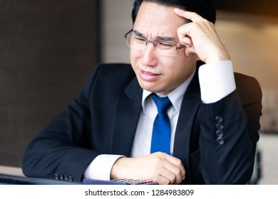 Sadness businessman crying which sitting at coffee shop, losing money from stock investment. Depressed man feel regret from unpleasant pain and holding forehead while situation failed, loss job
