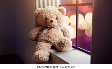Sadness and Loneliness Concept. Lonely Teddy Bear Toy Siting Alone beside Window in the Dark Room, City Night Light as Outside View