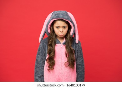 Sadness. Rest and relax. Cute bunny kid on red background. Baby animal character role. Gorgeous girl in bunny costume. Child in rabbit kigurumi. Sad girl in bunny pajamas. Depression concept.