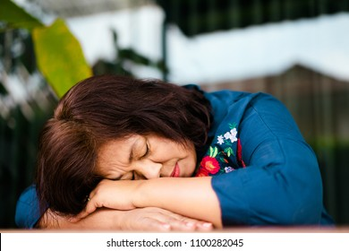 Sadness Senior Woman having a nap on the table relaxing with her head tilted down on the table and eyes closed
