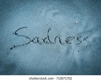 Sadness, word written on blue sand
