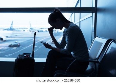 Sad/stressed/sick woman at the airport holding smart phone