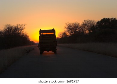 Safari vechicle driving romanticly into sunset
