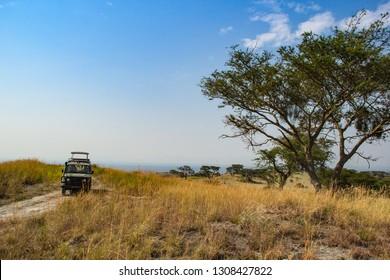 Safari vehicle on hill in savannah in Queen Elizabeth National Park in Uganda Africa