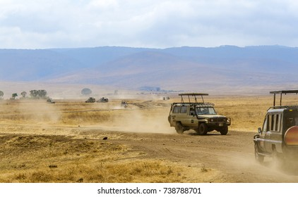 Safari vehicles driving on busy dirt road on floor of Ngorongoro Crater, looking for wildlife activity up close. Savannah landscape. Steep sides of crater in distance. Extinct volcano.Tanzania, Africa