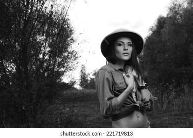 safari woman in swamp wearing safari hat standing on moss