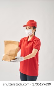 safe delivery woman in red dress, face mask and  gloves holding in hand paper bag