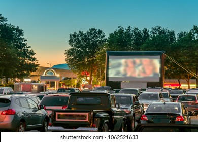 Safe entertainment and pastime for families during quarantine and isolation. Watching movies outdoors from the car in the city parking lot on a warm summer night