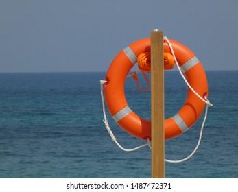 Safe holidays: Orange lifebuoy with orange rope on the beach, El Albir, Spain