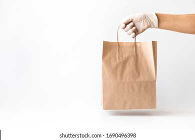 Сoncept of safe home delivery in a pandemic. Coronavirus 2019-nCov Protection. Courier  Paper bag hand in medical glove.Copy space .