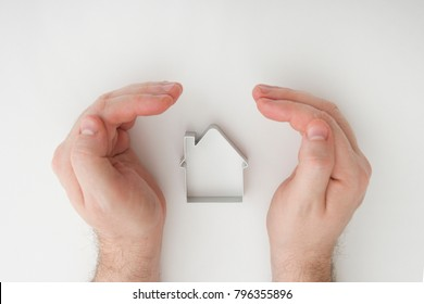 safe insulation home with businessman hands protecting the roof of a residential house to secure, care or insure for real estate coverage, top view