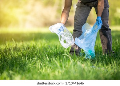 Safe the planet, man volunteer hand picking up garbage in forest for clean planet, environmentally and ecology friendly