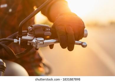 Sicheres Fahrkonzept. Makro links Hand des Motorradfahrers mit Reithandschuh auf der Kupplung. Outdoor Shooting auf der Straße mit Kopienraum