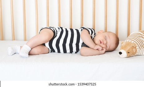 Safe sleeping for babies. Adorable newborn boy napping on his side in crib, clasping hands, panorama
