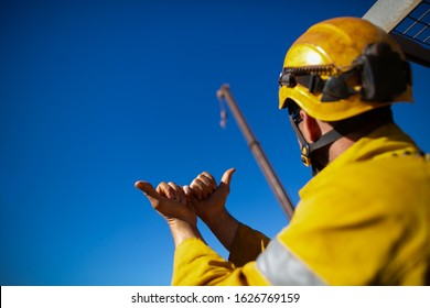 Safe work practice rigger wearing safety fall protection helmet giving crane driver hand signal by holding two hand against each other and pointing both thump meant crane boom is giging out slowly