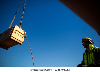 Safe work practices defocused rigger wearing hard hat standing outside suspended load danger dropped zone looking at the load while crane is lifting away at construction site, Perth, Australia