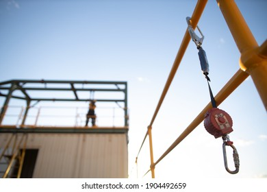 Safe work practices an inertia reel shock absorbing fall protection hook lanyard device clipping hanging on handrail with defocused construction worker working at heights in fall restraint background - Shutterstock ID 1904492659