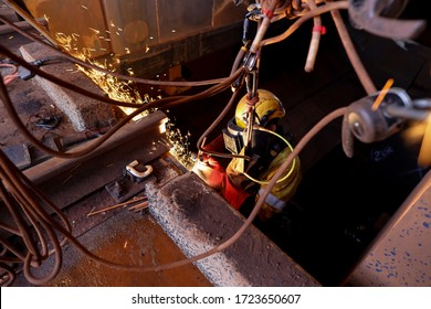 Safe work practices rope access abseiler worker wearing a fall industrial safety yellow helmet fall protection dark face shield, other safety PPE while commencing hot work gouging metal plate repairin