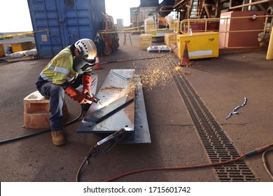 Safe work practices worker setting wearing a safety helmet, red welding safety leather glove dark face shield  protection while commencing hot work gouging metal plate on the ground surface