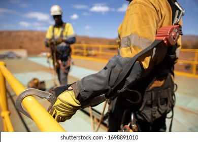Safe work practices worker wearing hand safety glove clipping an inertia reel shock absorbing fall protection hook  lanyard device on rail protection defocused supervisor making sure correctly safe