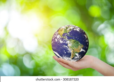 Safe world concept . Hand Holding world ball on white green bokeh.Copy Space on horizontal sheet.Elements of this image furnished by NASA.United Nations Climate Change Conference
