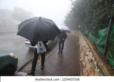 SAFED, ISRAEL - 12/7/2018: Orthodox Jews walk through the rain while holding umbrellas on a stormy day in Safed, Israel