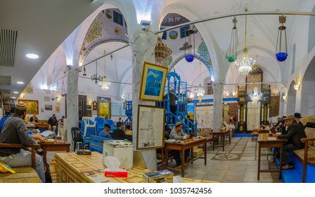 SAFED, ISRAEL - FEB 28, 2018: Traditional Purim (Jewish Holiday) in the old Abuhav synagogue with prayers, some in costumes, attend a reading of the megillah (Scroll of Esther). Safed (Tzfat), Israel