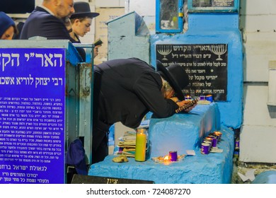SAFED, ISRAEL - SEPTEMBER 27, 2017: Jewish men pray Selichot (penitential pray), and kneel in pray, at the tomb of The ARI (Rabbi Isaac Luria), in the old cemetery of Safed (Tzfat), Israel